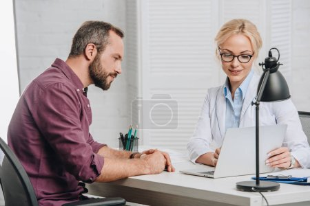 Photo for Side view of female chiropractor pointing at laptop screen during appointment with patient in hospital - Royalty Free Image