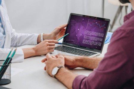 vista parcial del médico apuntando a la pantalla del ordenador portátil con el paciente cerca en el lugar de trabajo en el hospital