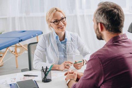 Photo pour Physiothérapeute souriant en manteau blanc regardant le patient pendant le rendez-vous à la clinique - image libre de droit