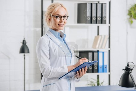 Photo pour Vue latérale du chiropraticien souriant en lunettes et manteau blanc avec bloc-notes en clinique - image libre de droit