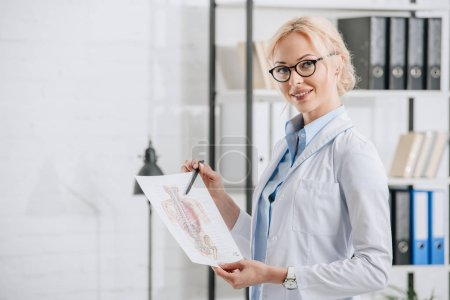 side view of smiling chiropractor in eyeglasses and white coat pointing at human body scheme in clinic