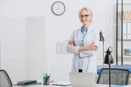 Photo for Portrait of smiling chiropractor in eyeglasses and white coat standing at workplace in clinic - Royalty Free Image