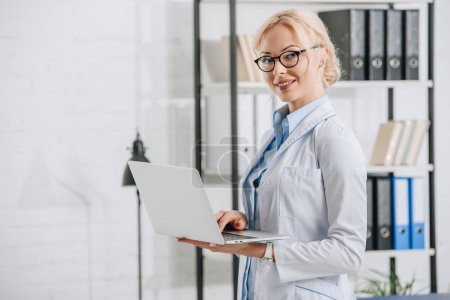 side view of smiling chiropractor in eyeglasses and white coat with laptop in clinic
