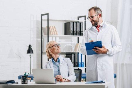 Photo pour Sourire des physiothérapeutes en blouse blanche regardant mutuellement au lieu de travail avec ordinateur portable en clinique - image libre de droit