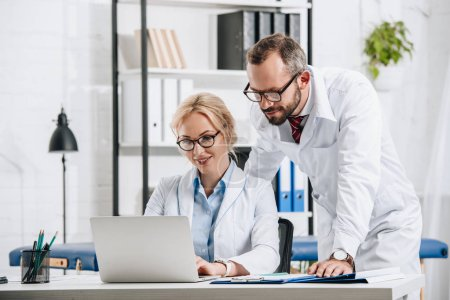 smiling physiotherapists in white coats using laptop together in clinic