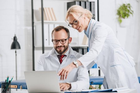 Photo pour Sourire des physiothérapeutes en blouse blanche, l'utilisation d'ordinateur portable sur la clinique - image libre de droit