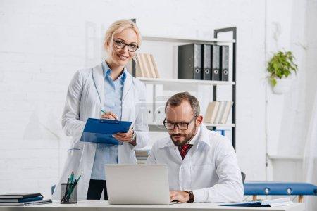 Photo pour Portrait de physiothérapeutes en blouse blanche et lunettes sur lieu de travail en clinique - image libre de droit