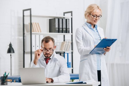 portrait of physiotherapists in white coats and eyeglasses at workplace in clinic