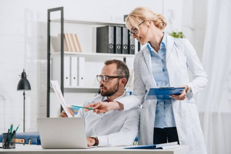 Photo for Portrait of physiotherapists in white coats discussing picture at workplace with laptop in clinic - Royalty Free Image