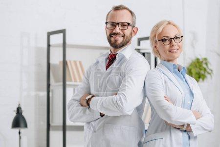 Photo pour Portrait de sourire des physiothérapeutes en blouse blanche, regardant la caméra en clinique - image libre de droit