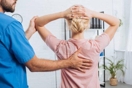 Photo pour Plan recadré de physiothérapeute faisant massage à la femme sur la table de massage à l'hôpital - image libre de droit