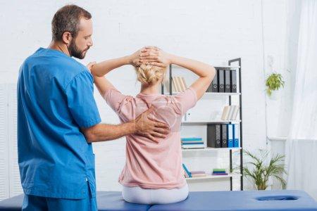 Photo pour Vue arrière du physiothérapeute faisant massage à la femme sur la table de massage à l'hôpital - image libre de droit