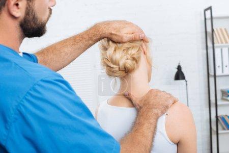 Photo pour Vue partielle du chiropraticien étirant le cou de la femme lors d'un rendez-vous à l'hôpital - image libre de droit