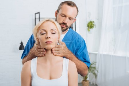 portrait of massage therapist massaging neck of young woman in clinic