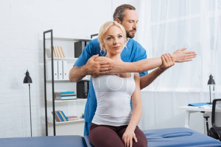 physiotherapist stretching patients arm on massage table in hospital