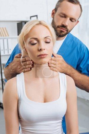 Photo pour Portrait de massothérapeute massant le cou de jeune femme en clinique - image libre de droit