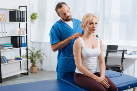 physiotherapist massaging womans shoulders on massage table in hospital
