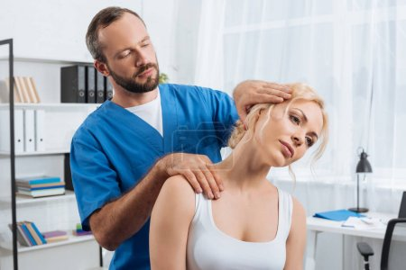 Photo for Portrait of chiropractor stretching neck of woman during appointment in hospital - Royalty Free Image