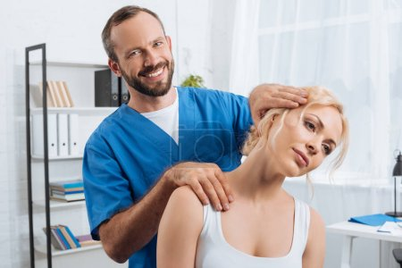 portrait of smiling chiropractor stretching neck of woman during appointment in hospital