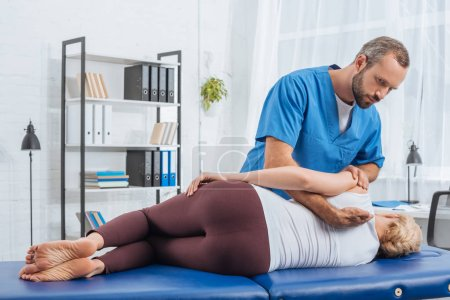 Photo for Chiropractor massaging back of patient that lying on massage table in hospital - Royalty Free Image