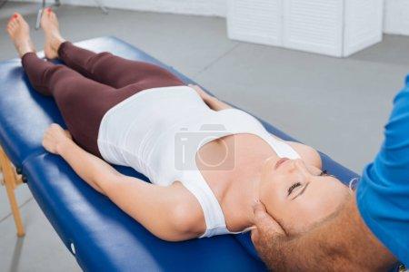 Photo pour Vue partielle du physiothérapeute massant le cou du patient couché sur la table de massage à la clinique - image libre de droit