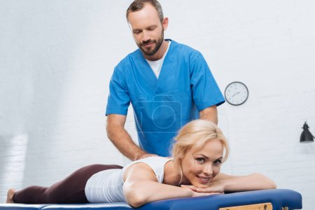 massage therapist doing massage to smiling woman on massage table in clinic