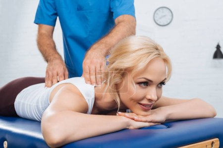 Photo for Partial view of massage therapist doing massage to smiling woman on massage table in clinic - Royalty Free Image
