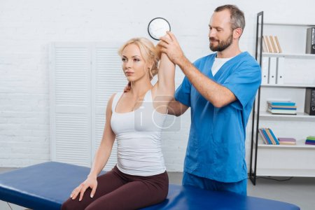 smiling chiropractor stretching womans arm on massage table in clinic