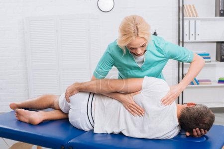 Photo for Chiropractor massaging back on patient on massage table in hospital - Royalty Free Image