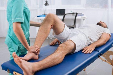 Photo pour Vue partielle du massothérapeute femelle faire massage au patient sur la table de massage en clinique - image libre de droit