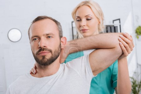portrait of physiotherapist stretching mans arm in hospital