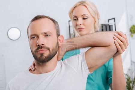 Photo pour Portrait de physiothérapeute étirant bras mans à l'hôpital - image libre de droit