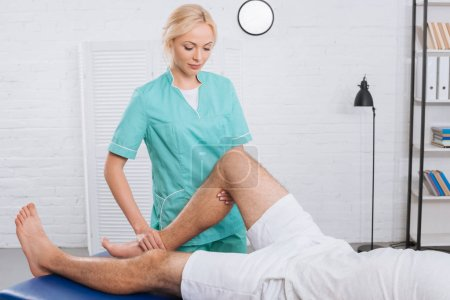 partial view of chiropractor massaging patients leg during appointment in clinic