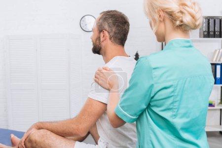Photo pour Vue latérale du massothérapeute faisant le massage au patient sur la table de massage à la clinique - image libre de droit