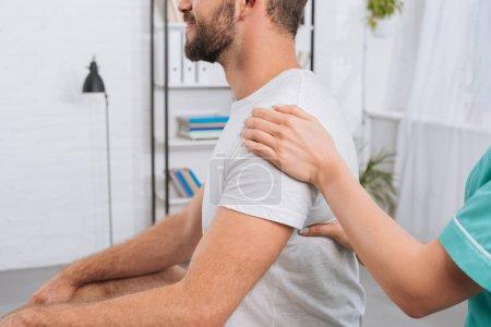 Photo pour Vue partielle du massothérapeute faisant le massage au patient en clinique - image libre de droit