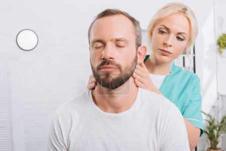 Photo for Portrait of physiotherapist massaging man neck in clinic - Royalty Free Image