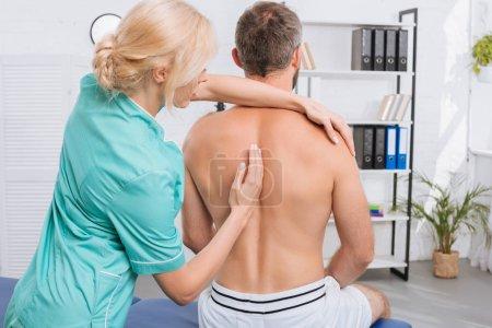 Photo pour Vue arrière de l'homme ayant un ajustement chiropratique à la clinique - image libre de droit