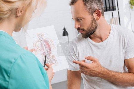 Photo pour Chiropratique montrant l'image du corps humain au patient masculin pendant le rendez-vous à la clinique - image libre de droit