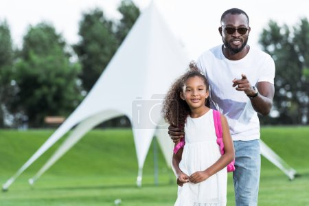 african american father pointing on camera to adorable daughter with school bag in park