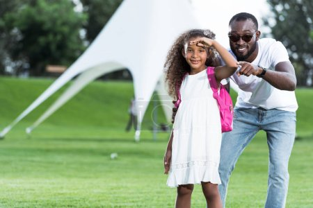 african american father pointing on camera to daughter with school bag in park