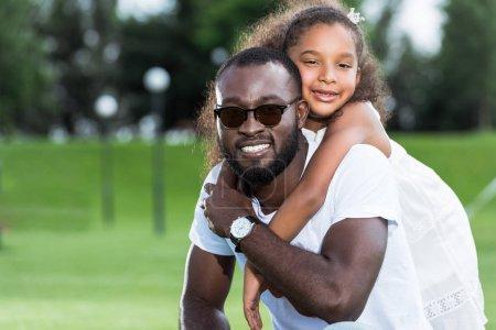 afro-américaine fille étreignant souriant père de retour dans le parc