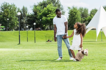 Photo for African american father and daughter with teddy bear holding hands and walking in park - Royalty Free Image