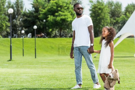 Photo for African american father and daughter holding hands and walking in park - Royalty Free Image
