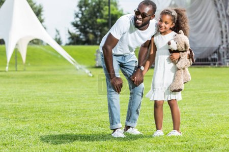 Photo for African american father and daughter holding hands in park and looking away - Royalty Free Image