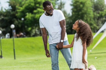 Photo for African american father and daughter holding hands and looking at each other in park - Royalty Free Image