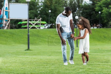 Photo for African american police officer with gun and daughter holding hands and walking in park - Royalty Free Image