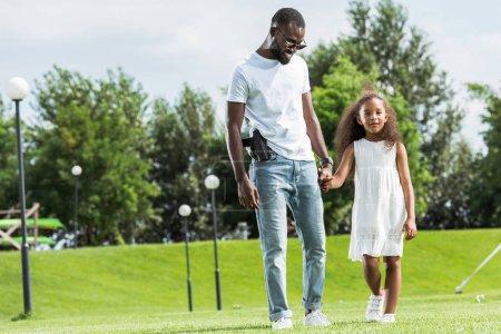 Photo pour Flic afro-américaine avec arme à feu dans l'étui et sa fille main dans la main et la marche au parc d'attractions - image libre de droit