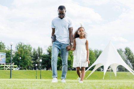 Photo pour Policier afro-américain avec pistolet et sa fille main dans la main et la marche au parc d'attractions - image libre de droit
