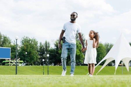 Foto de Americano africano agente de policía con arma y su hija tomados de la mano y caminando en el parque de atracciones - Imagen libre de derechos