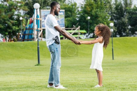 african american policeman with gun and daughter holding hands and spinning around in amusement park
